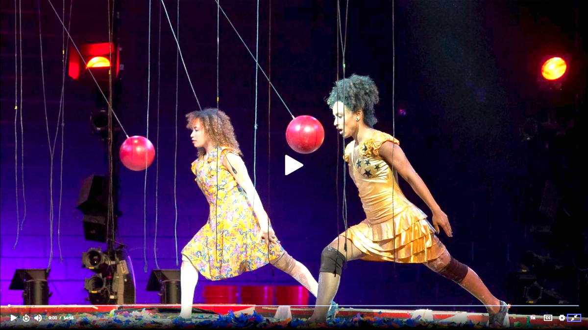 two dancers come face to face with swinging bowling balls